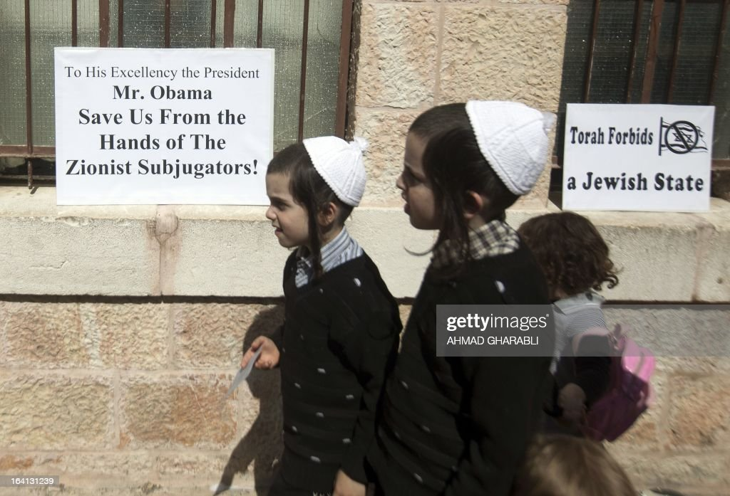 Ultra-Orthodox Jewish children walk past slogans of the Neturei Karta movement during a rally held by the small anti-Zionist Jewish faction, that opposes Israel's existence, in Jerusalems Mea Sharim district on March 20, 2013, as US President Barrack Obama landed in the Jewish state for the first time as US president. The US president is on a mission to ease past tensions with his hosts and hoping to paper over differences on handling Iran's nuclear threat.