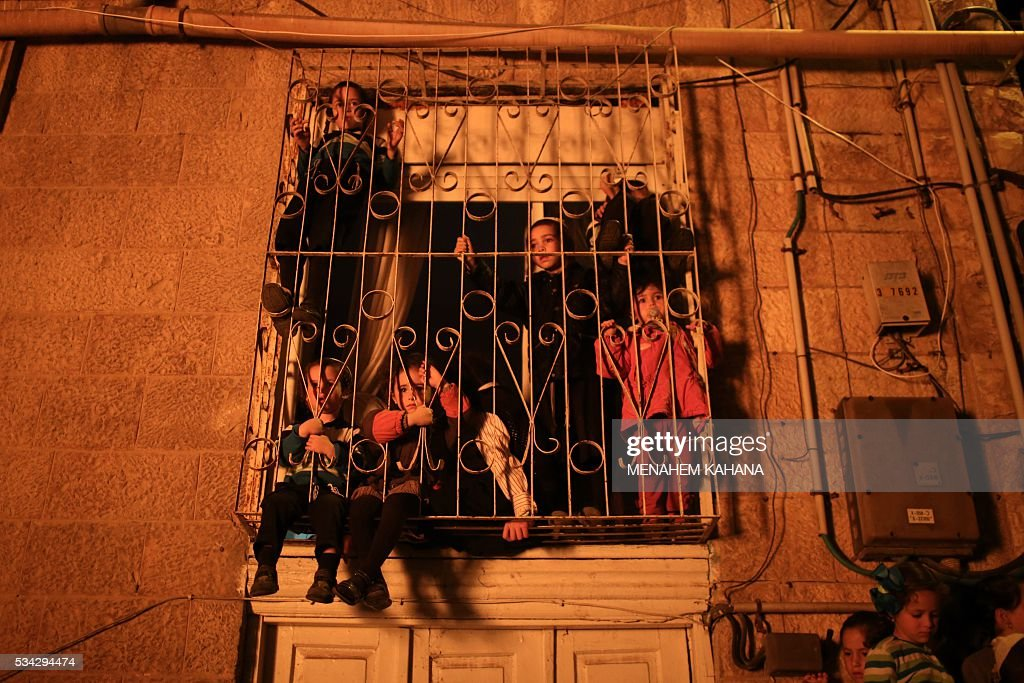 Ultra-Orthodox Jewish children watch the giant bonfire in the Mea Shearim neighborhood of Jerusalem on May 25,2016 during the celebration of Lag BaOmer. The Lag BaOmer bonfire is lit to commemorate the death of renowned Jewish scholar and renowned Bar Yochai some 1800 years ago. In a night long vigil thousands of Jews will light large bonfires and visit the final resting place of Bar Yochai, who is revered as one of Judaism's great sages. / AFP / MENAHEM