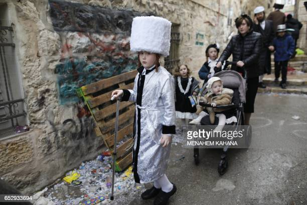 TOPSHOT UltraOrthodox Jewish children wearing costumes walk in Jerusalem's Mea Shearim ultraOrthodox neighbourhood on March 13 2017 during the...