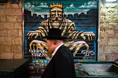 A ultraOrthodox Jewish man passes in front of a graffiti depicting King Solomon which was painted over a closed shutter at the Mahane Yehuda Market...