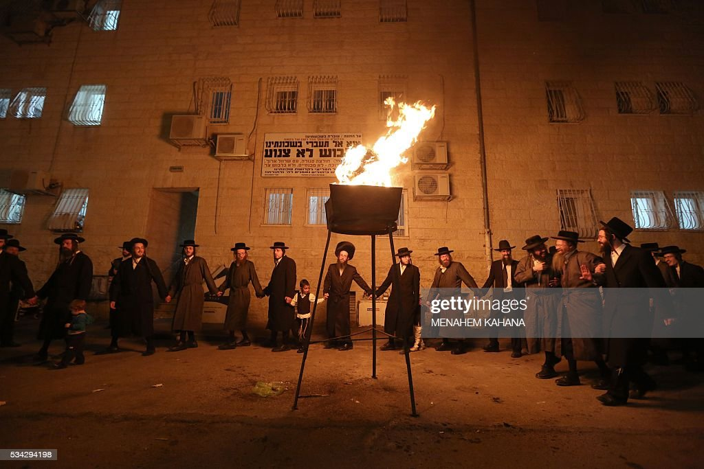 Ultra-Orthodox Jewish men dance as they light a giant oilfire in the Mea Shearim neighborhood of Jerusalem on May 25,2016 during the celebration of Lag BaOmer. The Lag BaOmer bonfire is lit to commemorate the death of renowned Jewish scholar and renowned Bar Yochai some 1800 years ago. In a night long vigil thousands of Jews will light large bonfires and visit the final resting place of Bar Yochai, who is revered as one of Judaism's great sages. / AFP / MENAHEM