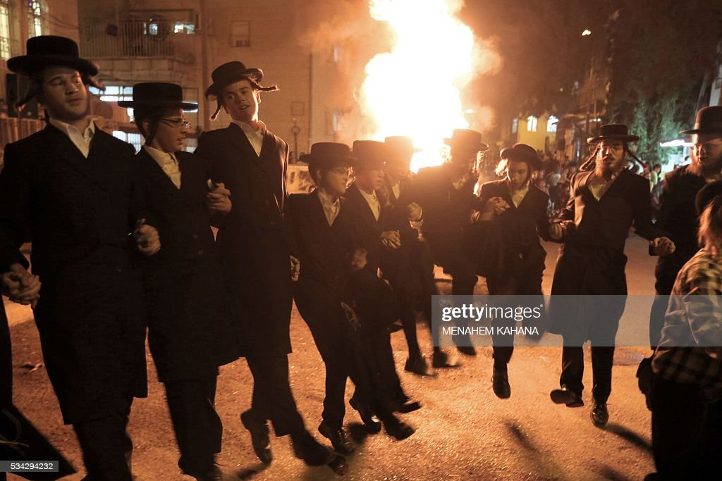 Ultra-Orthodox Jewish men dance as they light a giant oilfire in the Mea Shearim neighborhood of Jerusalem on May 25, 2016 during the celebration of Lag BaOmer. The Lag BaOmer bonfire is lit to commemorate the death of renowned Jewish scholar and renowned Bar Yochai some 1800 years ago. In a night long vigil thousands of Jews will light large bonfires and visit the final resting place of Bar Yochai, who is revered as one of Judaism's great sages. / AFP / MENAHEM
