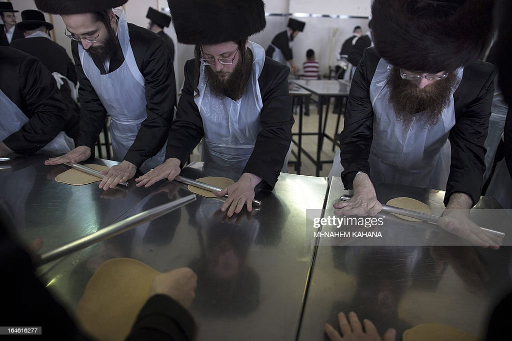 Ultra-Orthodox Jewish men knead dough before baking the matzoth or unleavened bread for the Pesach holiday (Passover) in Jerusalem on March 25, 2013. Religious Jews throughout the world eat matzoth during the eight-day Pesach holiday (Passover), which begins on March 25 at sunset and commemorates the Israelites' exodus from slavery in Egypt some 3,500 years ago and their plight by refraining from eating leavened food products.
