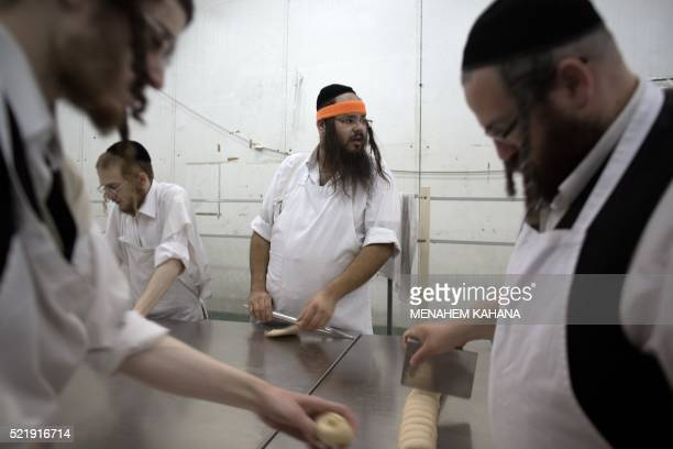 UltraOrthodox Jewish men knead the dough before baking Matzoth on April 17 2016 at a bakery in the Israeli city of Ashdod south of Tel Aviv Religious...