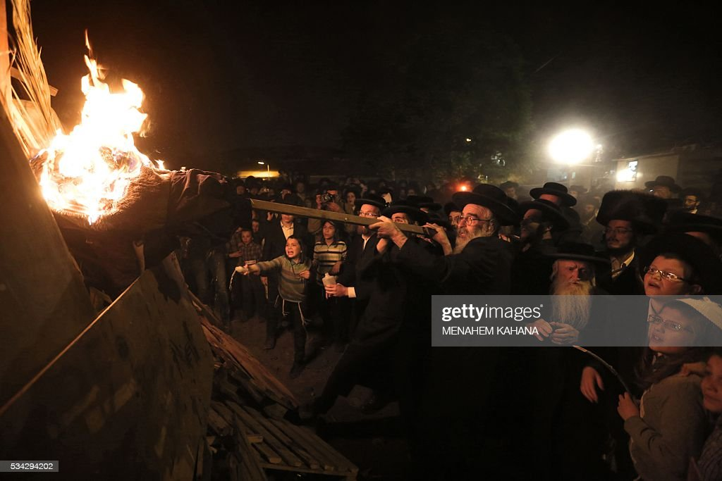 Ultra-Orthodox Jewish men light a giant oilfire in the Mea Shearim neighborhood of Jerusalem on May 25,2016 during the celebration of Lag BaOmer. The Lag BaOmer bonfire is lit to commemorate the death of renowned Jewish scholar and renowned Bar Yochai some 1800 years ago. In a night long vigil thousands of Jews will light large bonfires and visit the final resting place of Bar Yochai, who is revered as one of Judaism's great sages. / AFP / MENAHEM