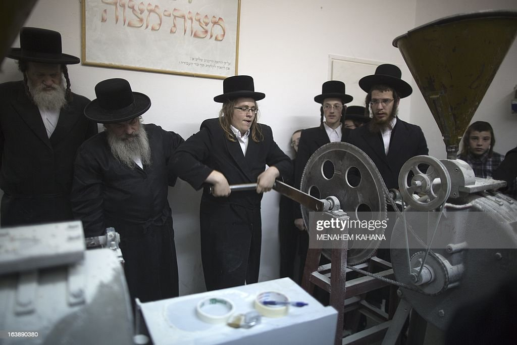Ultra-Orthodox Jewish men manually grind flour to be used for making of the Matzoth or unleavened bread on March 17, 2013, in Jerusalem. Religious Jews throughout the world eat matzoth during the eight-day Pesach holiday (Passover), which begins the March 25, with the sunset to commemorate the Israelis' exodus from Egypt some 3,500 years ago and commemorate their ancestors' plight by refraining from eating leavened food products.
