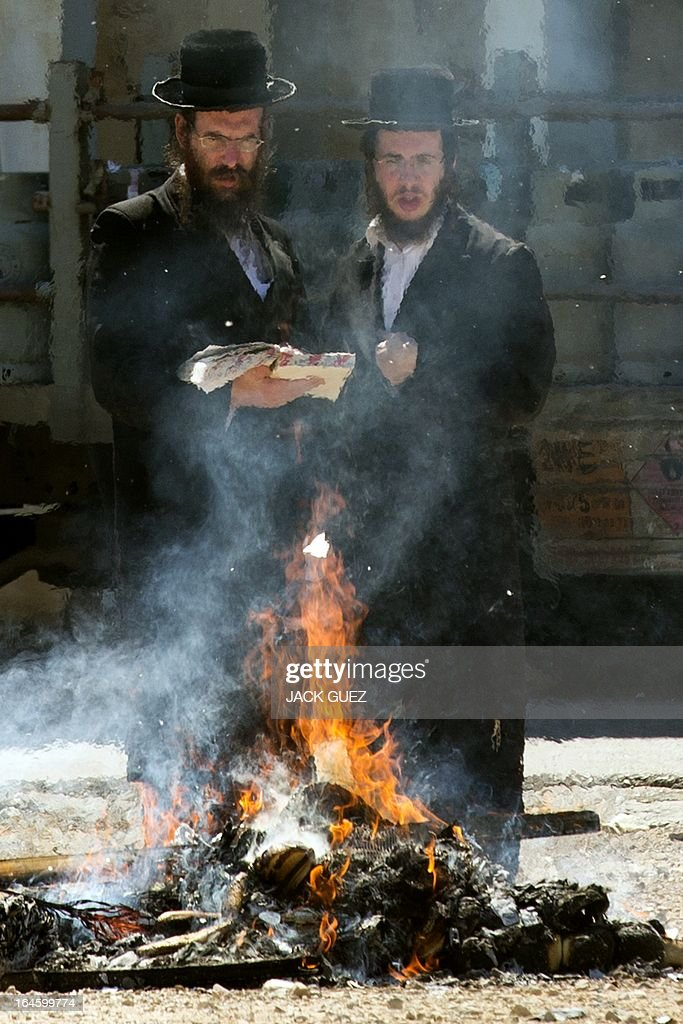 Ultra-Orthodox Jewish men pray as leavened items are burnt in the final preparation before the start at sundown of the Jewish Passover holiday, in the Mediterranean coastal city of Netanya, central Israel, on March 25, 2013. All leavened food, such as bread, is forbidden to Jews during the week-long holiday, which to commemorate the Israelites' exodus from Egypt some 3,500 years ago. Due to the haste with which the Jews left Egypt, the bread they had prepared for the journey did not have time to rise. To commemorate their ancestors' plight, the religious avoid eating leavened food products throughout Passover. AFP PHOTO / JACK GUEZ