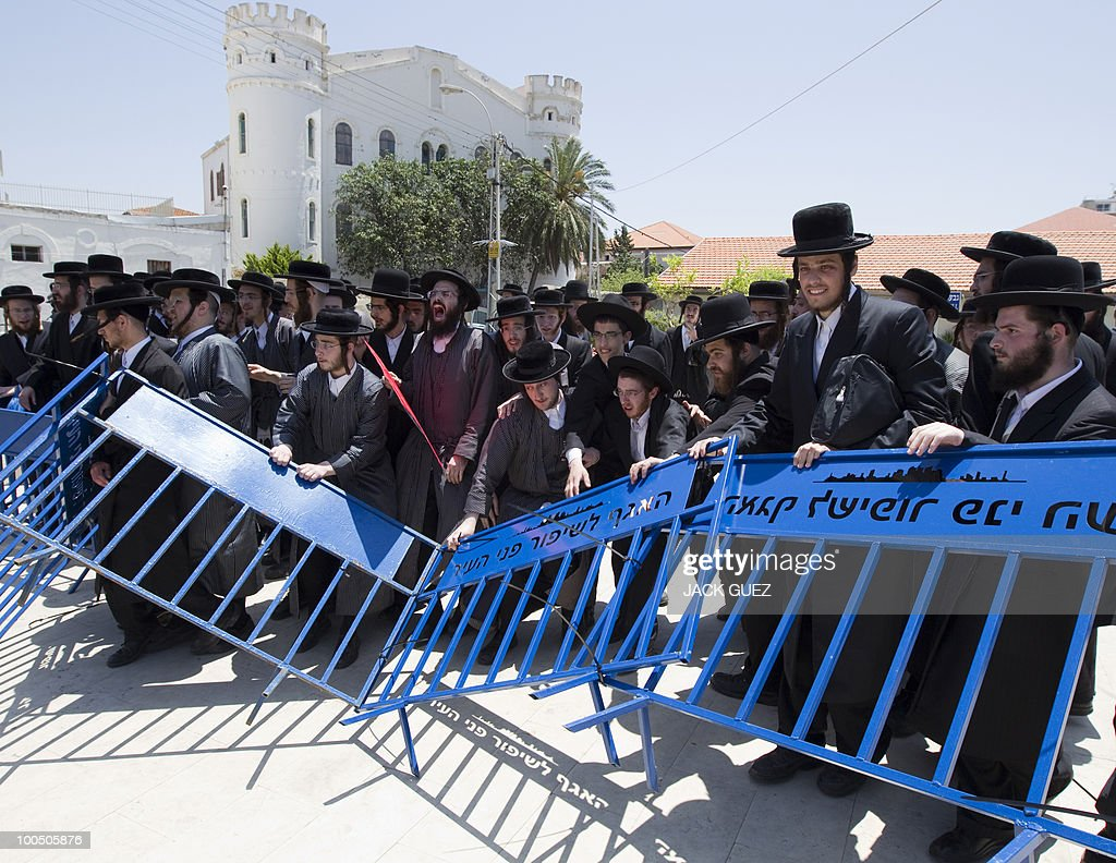 Ultra-Orthodox Jewish men pull metal barriers separating them from Israeli policemen during a protest against the removal of ancient tombs in Tel Aviv on May 25, 2010. The remains were exhumed from ancient graves located near the Barzilai hospital in the southern town of Ashkelon last week so that an emergency ward designed to resist rockets can be built to serve residents living near the Hamas-ruled Gaza Strip.