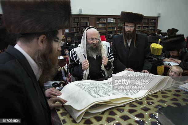 UltraOrthodox Jewish men read the book of Esther at a synagogue in the Israeli city of Beit Shemesh on March 23 2016 during the feast of Purim The...