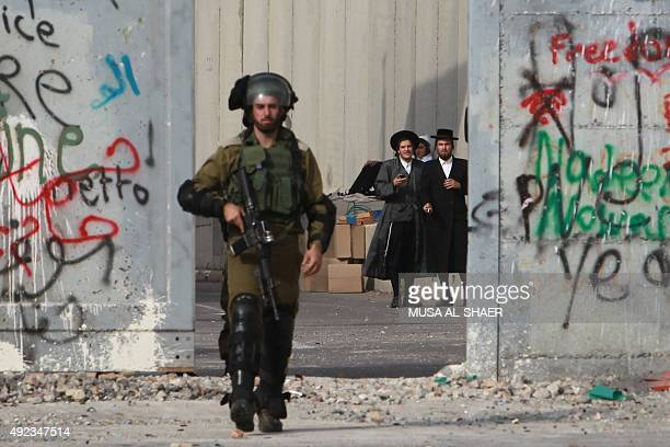 UltraOrthodox Jewish men stand behind a section of Israel's controversial separation wall as an Israeli soldier makes his way at the main entrance of...