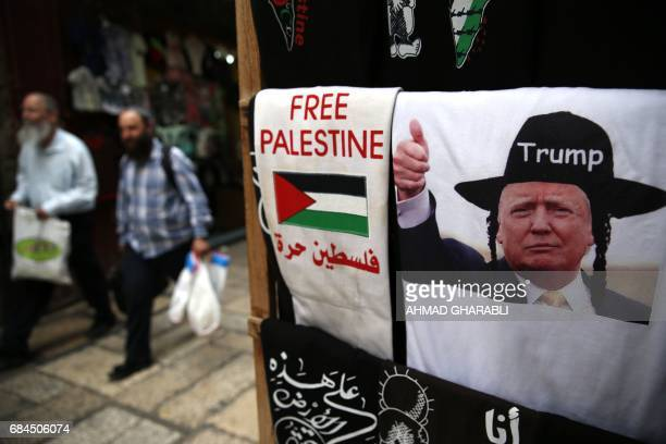 UltraOrthodox Jewish men walk past a souvenir shop displaying a Tshirt bearing an image of US President Donald Trump dressed as a Hasidic Jew in...