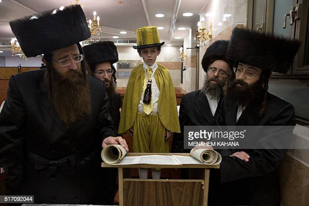 TOPSHOT UltraOrthodox Jews and a dressed up boy read the book of Esther at a synagogue in the Israeli city of Beit Shemesh on March 23 2016 during...