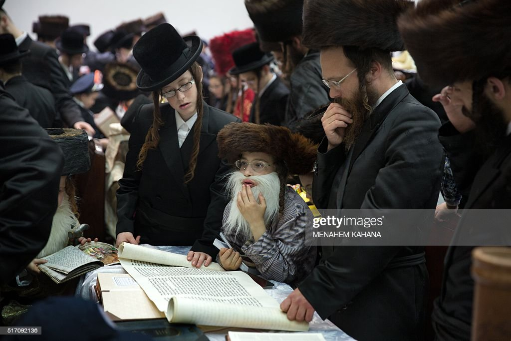 UltraOrthodox Jews and dressed up children read the book of Esther at a synagogue in the Israeli city of Beit Shemesh on March 23 2016 during the...