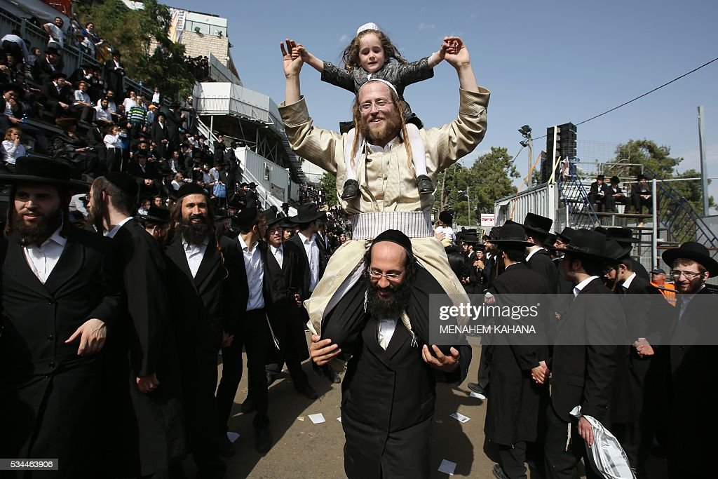Ultra-Orthodox Jews dance at the grave site of Rabbi Shimon Bar Yochai in the northern Israeli village of Meron on May 26, 2016, at the start of the day-long holiday of Lag Baomer that commemorates the Jewish scholar's death. Thousands of religious Jews light large bonfires all night long and visit the shrine of Bar Yochai, one of the most prominent sages in Jewish history, during the holiday. / AFP / MENAHEM