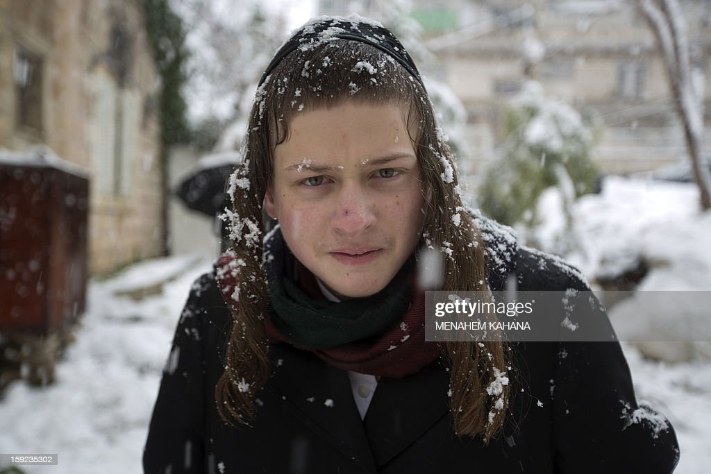 Ultra-orthodox Jews enjoy the snow in the Mea Shearim religious neighborhood of Jerusalem on January 10, 2013. Jerusalem was transformed into a winter wonderland after heavy overnight snowfall turned the Holy City and much of the region white, bringing hordes of excited children onto the streets. AFP PHOTO/MENAHEM KAHANA