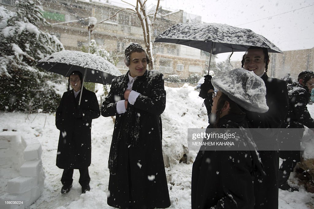 Ultra-orthodox Jews enjoys the snow in the Mea Shearim religious neighborhood of Jerusalem on January 10, 2013. Jerusalem was transformed into a winter wonderland after heavy overnight snowfall turned the Holy City and much of the region white, bringing hordes of excited children onto the streets. AFP PHOTO/MENAHEM KAHANA