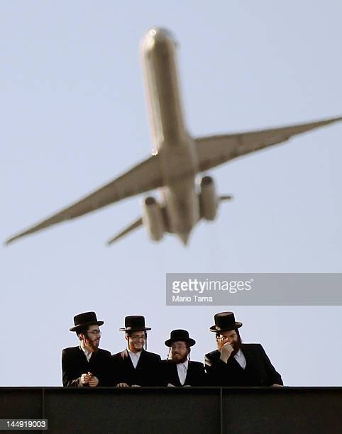UltraOrthodox Jews gather at Citi Field as a plane takes off overhead from LaGuradia Airport at a meeting to discuss the risks of using the Internet...