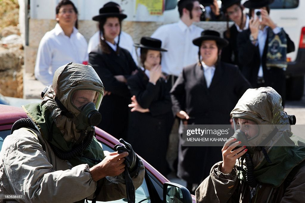 Ultra-orthodox Jews look at Israeli soldiers from the army's Home Front Command wearing a chemical warfare suits taking part in a defence drill simulating a chemical missile attack in the central Israeli city of Beit Shemesh, on October 2 2013.
