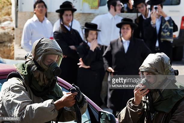 Ultraorthodox Jews look at Israeli soldiers from the army's Home Front Command wearing a chemical warfare suits taking part in a defence drill...