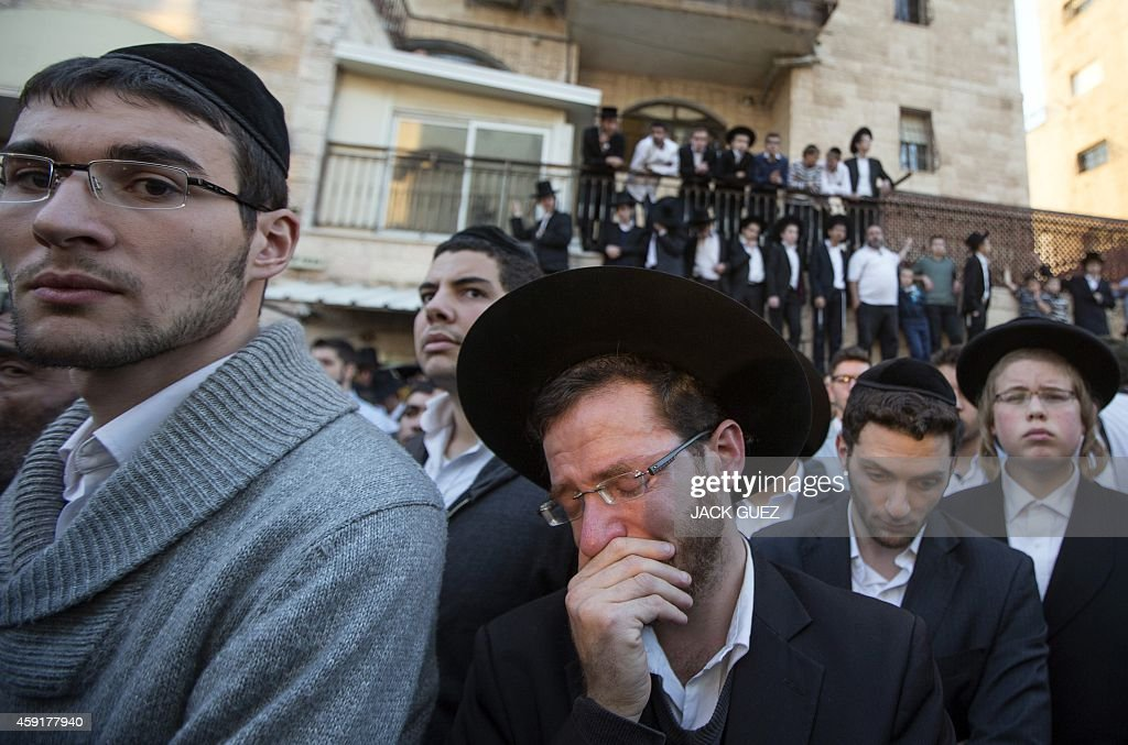UltraOrthodox Jews mourn over the bodies of three of the victims of an attack by two Palestinians on Jewish worshippers killing four Israelis at a...