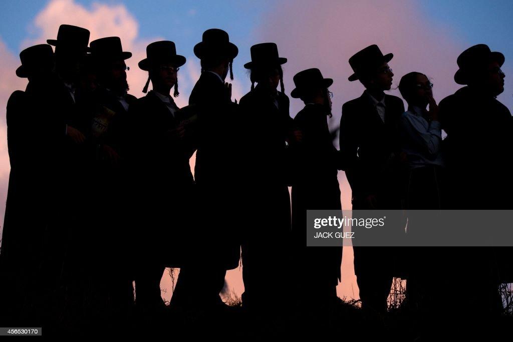 UltraOrthodox Jews pray along the Ayarkon River in the city of Ramat Gan near Tel Aviv during the ritual of 'Tashlich' on October 2 2014 Tashlich is...