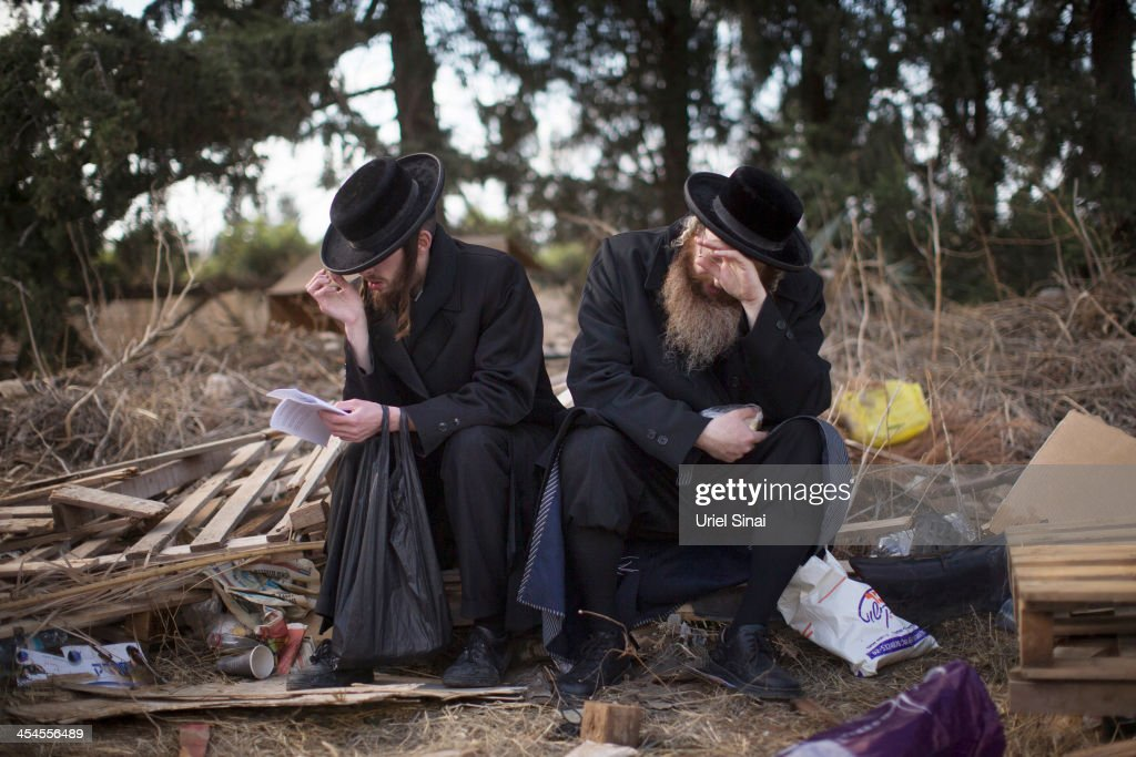 UltraOrthodox Jews pray as they gather during a protest against their military conscription outside a military prison on December 9 2013 in Atlit...