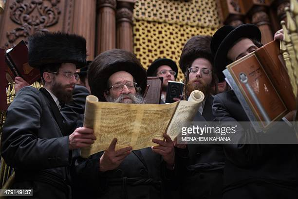 UltraOrthodox Jews read the Book of Esther at a synagogue in Jerusalem on March 16 2014 during the feast of Purim The carnivallike Purim holiday is...