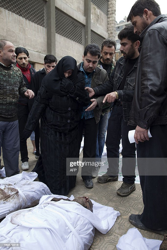 Um Mohammad identifies the body of her nephew Omar Jamil Akhras amongst the bodies of Syrian civilians executed and dumped in the Quweiq river, in the grounds of the courtyard of the Yarmouk School, in the Bustan al-Qasr district of Aleppo on January 30, 2013. Syria's opposition charged that 'global inaction' was giving Bashar al-Assad's regime a license to kill, a day after dozens of young men were found shot execution-style in the city of Aleppo.