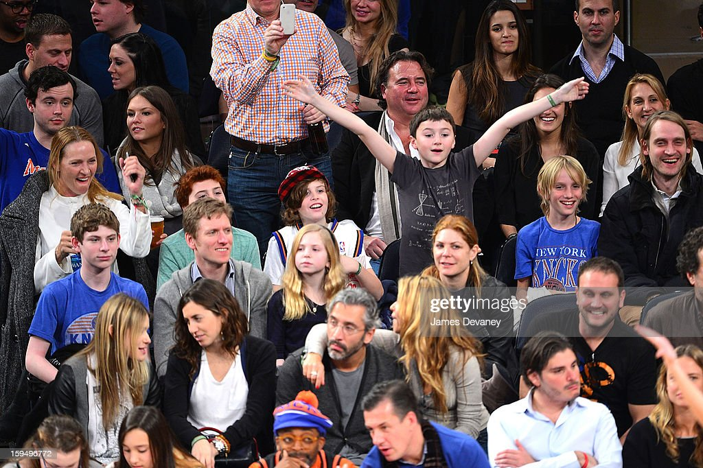 Uma Thurman (L), Levon Roan Thurman-Hawke (2nd from R) and Mipam Thurman (R) attend the New Orleans Hornets vs New York Knicks game at Madison Square Garden on January 13, 2013 in New York City.