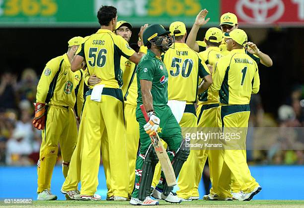 Umar Akmal of Pakistan looks dejected after losing his wicket as the Australian team celebrate during game one of the One Day International series...