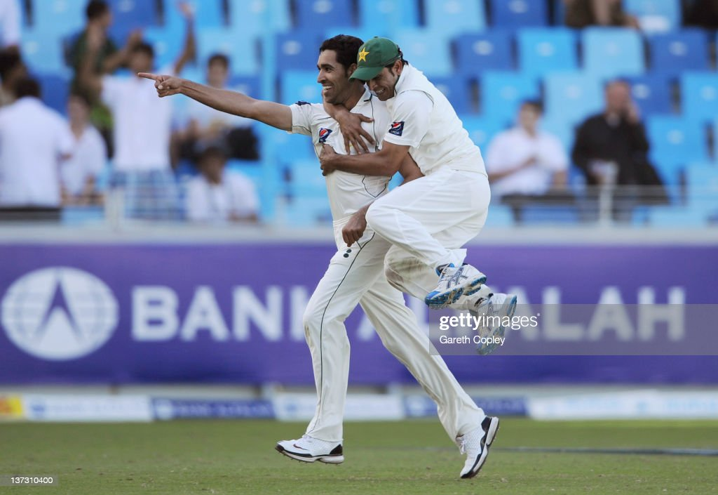 Umar Gul of Pakistan celebrates with Abdur Rehman after dismissing Jonathan Trott of England during the first Test match between Pakistan and England at The Dubai International Cricket Stadium on January 19, 2012 in Dubai, United Arab Emirates.
