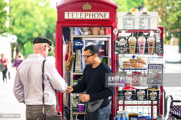 Umar Khalid coowner of the Kape Barako red telephone box coffee stall serves a customer on Hampstead High Street in London UK on Wednesday Aug 3 2016...