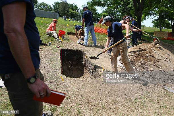 UMass Graduate Student Hannah Desmarais refills one of the excavation units at the UMass Boston Archaeological dig at Burial Hill in Plymouth Mass