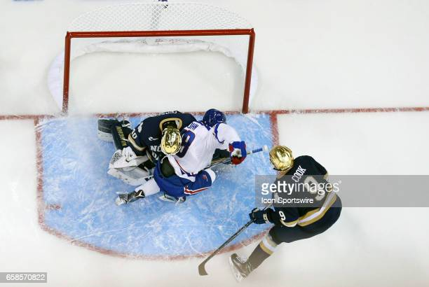 UMass Lowell River Hawks center Ryan Lohin crashes into Notre Dame Fighting Irish goaltender Cal Petersen during the NCAA Northeast Regional final...