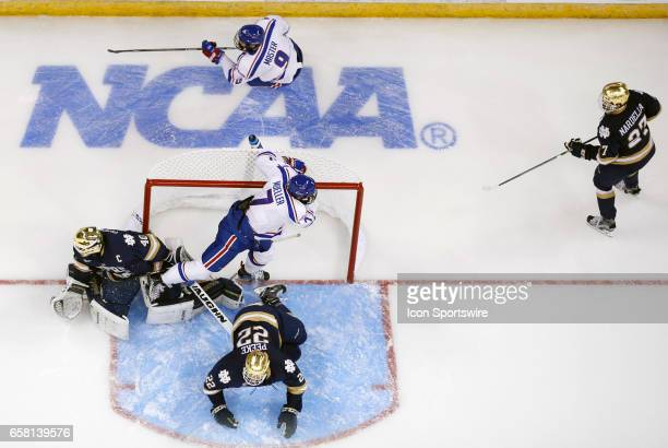 UMass Lowell River Hawks defenseman Tyler Mueller gets tied up with Notre Dame Fighting Irish goaltender Cal Petersen during the NCAA Northeast...