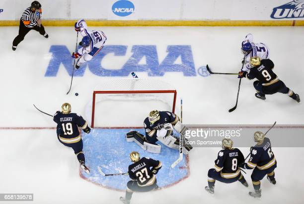 UMass Lowell River Hawks right wing John Edwardh tries to center the puck on Notre Dame Fighting Irish goaltender Cal Petersen during the NCAA...