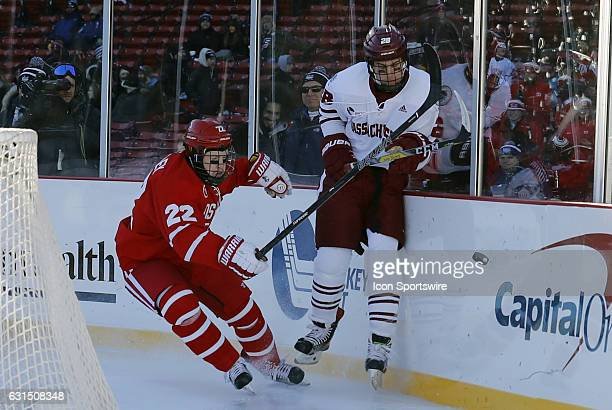 UMass Minutemen defenseman Jake McLaughlin avoids the hit from Boston University Terriers forward Tommy Kelley during a Frozen Fenway NCAA Men's...