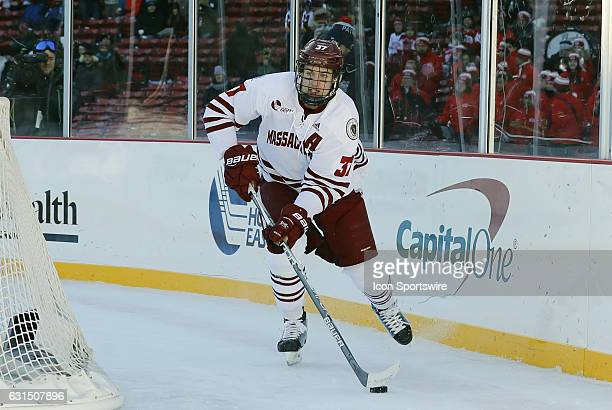 UMass Minutemen defenseman William Lagesson looks to clear the puck during a Frozen Fenway NCAA Men's Division 1 hockey game between the Boston...