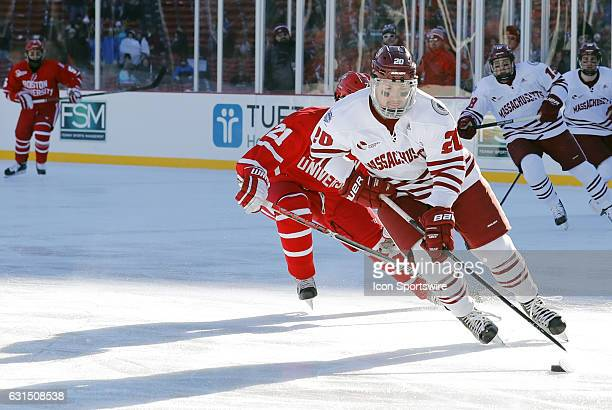 UMass Minutemen forward Brett Boeing skates the puck away from Boston University Terriers forward Patrick Harper during a Frozen Fenway NCAA Men's...