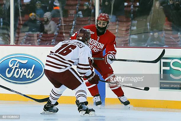 UMass Minutemen forward Steven Iacobellis lines up Boston University Terriers defenseman Chad Krys during a Frozen Fenway NCAA Men's Division 1...