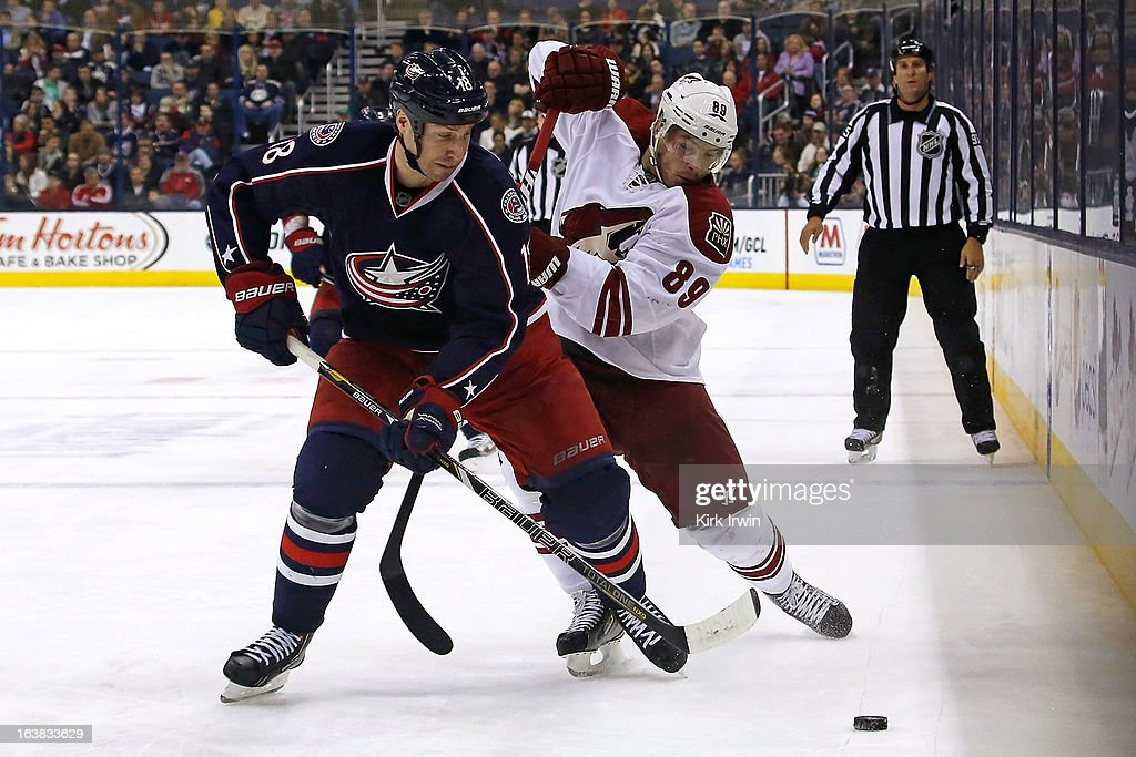 R.J. Umberger #18 of the Columbus Blue Jackets and Mikkel Boedker #89 of the Phoenix Coyotes battle for control of a loose puck during the second period on March 16, 2013 at Nationwide Arena in Columbus, Ohio.
