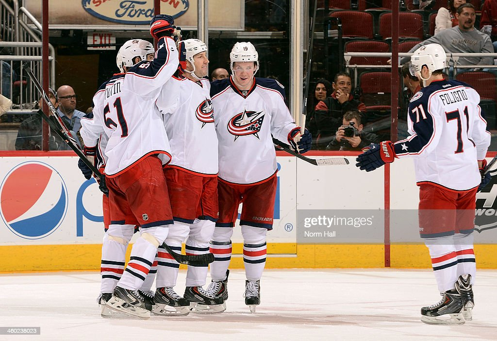 R.J. Umberger #18 of the Columbus Blue Jackets celebrates with teammates Fedor Tyutin #51, Ryan Johansen #19 and Nick Foligno #71 after Umberger's third-period goal against the Phoenix Coyotes at Jobing.com Arena on January 2, 2014 in Glendale, Arizona.