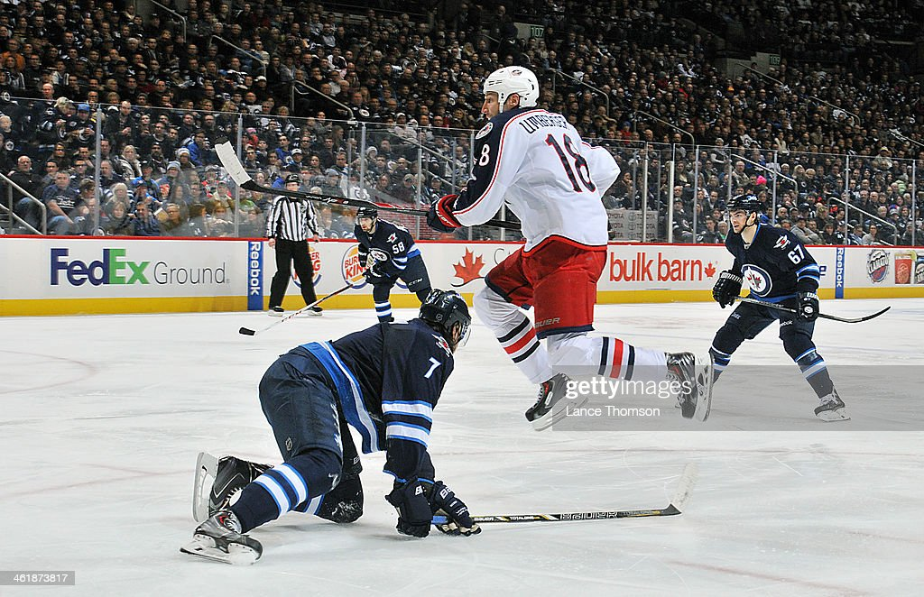 RJ Umberger #18 of the Columbus Blue Jackets jumps over the stick of a fallen <a gi-track='captionPersonalityLinkClicked' href=/galleries/search?phrase=Keaton+Ellerby&family=editorial&specificpeople=4111546 ng-click='$event.stopPropagation()'>Keaton Ellerby</a> #7 of the Winnipeg Jets during third period action at the MTS Centre on January 11, 2014 in Winnipeg, Manitoba, Canada.