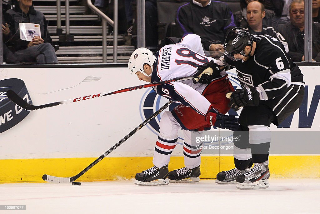 R.J. Umberger #18 of the Columbus Blue Jackets protects the puck along the right wing boards from <a gi-track='captionPersonalityLinkClicked' href=/galleries/search?phrase=Jake+Muzzin&family=editorial&specificpeople=7205557 ng-click='$event.stopPropagation()'>Jake Muzzin</a> #6 of the Los Angeles Kings in the third period during the NHL game at Staples Center on April 18, 2013 in Los Angeles, California. The Kings defeated the Blue Jackets 2-1.