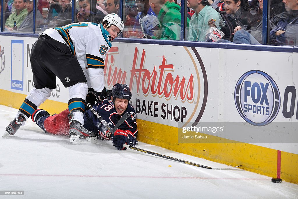 R.J. Umberger #18 of the Columbus Blue Jackets reaches out to a loose puck after being hit by Justin Braun #61 of the San Jose Sharks during the third period on April 9, 2013 at Nationwide Arena in Columbus, Ohio. Columbus defeated San Jose 4-0.
