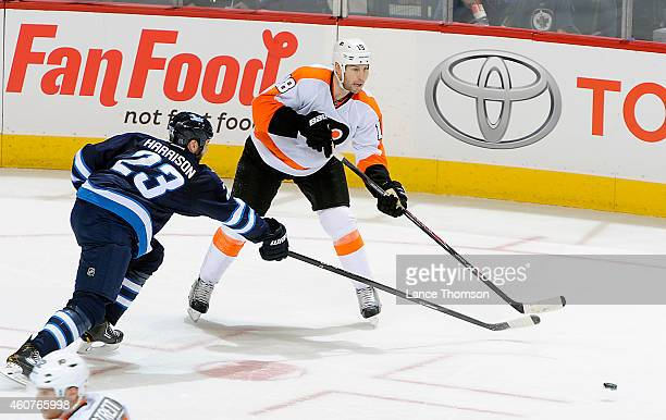 J Umberger of the Philadelphia Flyers passes the puck as Jay Harrison of the Winnipeg Jets defends during second period action on December 21 2014 at...