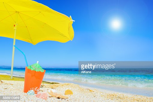 umbrella and cocktail under a shining sun : Stock Photo