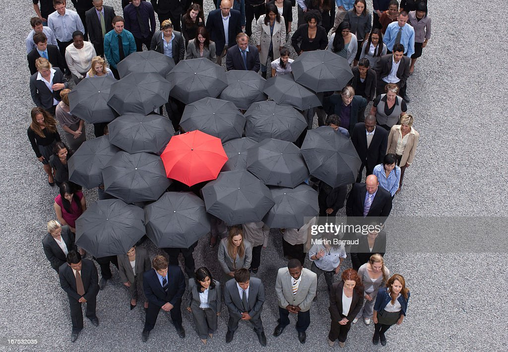 Umbrella at center of circle formed by business people : Stock Photo