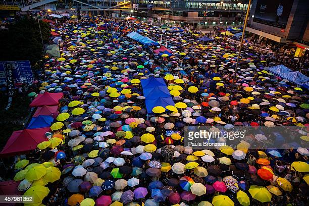 Umbrellas are opened as tens of thousands come to the main protest site one month after the Hong Kong police used tear gas to disperse protesters...