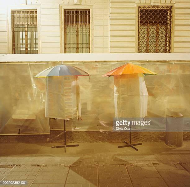Umbrellas covering postcard racks, outdoors